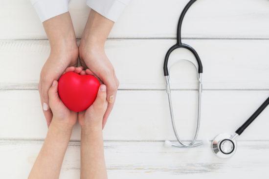Manos que sostienen un corazón rojo, representan la relación del profesional de la salud y sus pacientes
